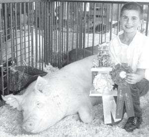 Eli Grieser, 11, Pettisville, with his crossbred gilt hog, which was named reserve grand champion in heavyweight hog judging in the 2011 Fulton County Junior Fair competition. Grieser also won second place in the showmanship competition for his age group.