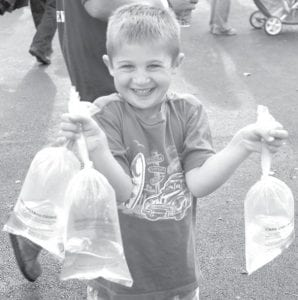 Brady Bacik, 5, Archbold, shows off the three goldfish he and his sister Eliza won at the 2011 Fulton County Fair.
