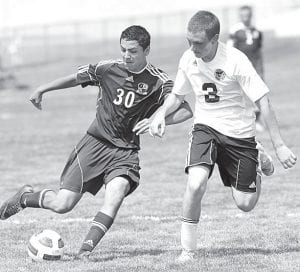 Archbold's Shae Hernandez tries to score while Pettisville defender Jacob Deffely tries to stop him.– photo by Mary Huber