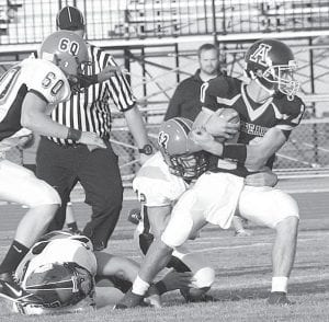 Blue Streak quarterback Evan Wyse tries to escape the grip of the Hicksville defense. The junior rushed for 106 yards and passed for 170 in Archbold's 19-14 victory.– photo by Scott Schultz