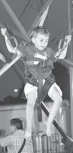 Braylon Wyse, 3, Archbold, had fun bouncing with bungee cords during the Fulton County Fair. He is the son of Jamison and Megan.– photo by Mary Huber