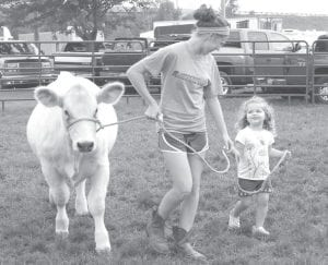 The Fulton County Fair means 4-H, food, and fun. Clockwise from top: Neila Kinsman, a freshman at Archbold High School, and Aspen Brehm, 2, Fayette, exercise Aspen's calf,