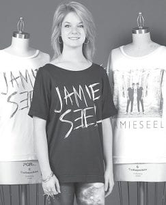 """Jamie Seel, AHS '10, with some of the t-shirts she designed. Working toward a career in fashion design, she spent the past 13 months studying in Los Angeles, Calif. Shirts are just part of a line of apparel she is developing under her own """"Jamie Seel"""" label.– photo courtesy Fashion Institute of Design & Marketing, LA"""