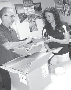 Brent Gnagey, Archbold Area School District technology director, and Lorinda Brader, technology assistant, unpack the first of 360 Apple iPad tablet computers, which arrived Friday, Aug. 31. Each Archbold High School student will receive soon one of the tablets.– photo by David Pugh