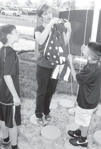 On the first day of school, Wednesday, Aug. 22, Dorothy Lambert, center, Archbold Elementary School principal, instructs fourth graders Joshua Nofziger, left, and Isaac Baumgartner on how to raise the American flag.– photo by David Pugh.