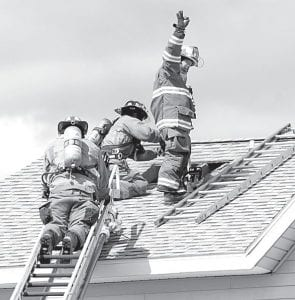 Marv Wheeler, Wauseon Fire Department chief, signals from the roof of a home in the 16000 block of Co. Rd. 19 that caught fire Sunday afternoon, Sept. 9. The Wauseon Fire Department was called to assist Fayette, which also received support from fire departments from Archbold, Lyons, and Morenci, Mich.– photo by Mary Huber