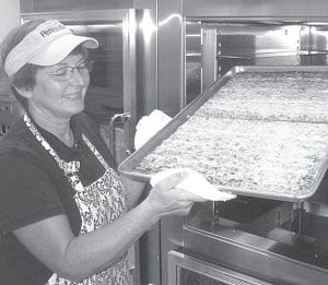 Brenda Aeschliman, head cook for the Pettisville Local School district, removes a tray of garlic flatbread from an oven in the school kitchen. In addition to more fresh fruits and vegetables, Aeschliman said the kitchen staff is trying to add more variety to the lunch menus.– photo by David Pugh