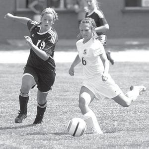 Archbold's Rebecca Schmucker kicks the ball forward to a teammate in AHS girls soccer action earlier this season.– photo by Mary Huber