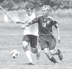 Archbold's Alex Hurst (19) and Pettisville's Matt Storrer battle for control of the ball in boys soccer action, Saturday, Aug. 25.– photo by Mary Huber