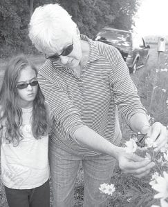 The Fulton County Soil and Water Conservation District hosted its third Monarchs & More family fun day, Sunday, Sept. 9, on property owned by Ed and Carol Nofziger west of Co. Rd. 19 on St. Rt. 2. Top: Laura Nafziger, Pettisville, gently places a Monarch butterfly on a wildflower as her granddaughter, Brook Fetter, 9, Adrian, Mich., watches. Bottom: The butterfly steps off Nafziger's hand onto the petals of a wildflower.– photos by David Pugh