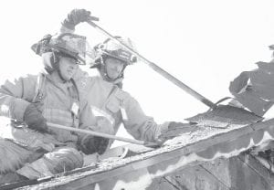 Kris Lauber, left, and Duane Beck, Archbold firefighters, remove roofing material from a home in the 1700 block of Co. Rd. 16 that caught fire Saturday, Sept. 15. AFD was one of four fire departments that responded.– photo by David Pugh