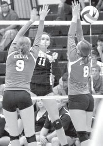 The spike of Pettisville's Dana Fricke (11) gets through two Delta blockers.– photo by Mario Gomez
