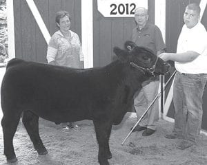 Grand champion beef feeder calf exhibitor Kaitlyn Nofziger (not pictured, pictured is Justin Nofziger, right), daughter of Greg & Jodi, Wauseon. Buyers, from left: Al Nofziger family, represented by Joyce Nofziger; Fulton County Cattle Feeders; Archbold Equipment, represented by Daryl Nofziger; Raymond Stutzman; Nofziger Farm Service; and Dean and J.R. Nofziger.