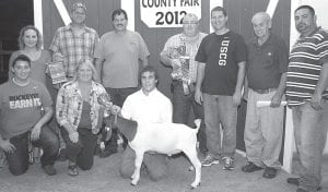 Grand champion market goat exhibitor Tony Banister, son of Chad and Kris, Wauseon. Buyers, front row from left: Shehorn Pizza, represented by Rick and Jill Shehorn; Fayette Feed Mill, represented by Fred Stockburger; Edward Jones, represented by Ron Hodges; J&B Feed Co., represented by B. Neuenschwander; Falor Farm Center, represented by Troy Najarian. Back row: Keil Farms, represented by Ashley Foord, Doug Keil and Chad Keil.