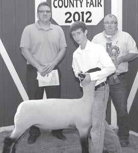 Grand champion market lamb exhibitor Troy King, right, son of Duane & Jenifer, Pettisville. Buyers, from left: Huntington Bank, represented by A.J. Genter; Fayette Feed Mill, represented by Fred Stockburger.