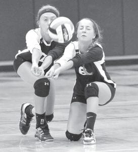 Emily Eicher, left, and Carley Hoffmire dig the volleyball in a recent match.– photo by Mario Gomez