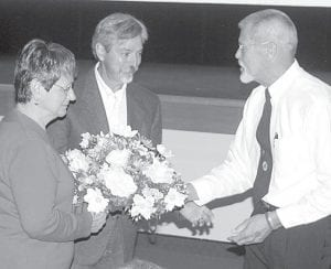 Lenny Miller, far right, an officer with the Archbold American Legion post, presents flowers to Terry Aeschliman and Cindy Winzeler, brother and sister of David Aeschliman, an AHS graduate who was killed in Vietnam. The presentation was made during a program at the high school, Thursday, Sept. 20.– photo by David Pugh