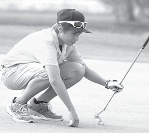 Evan King analyzes the green before putting earlier this season.– photo by David Pugh