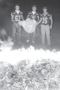 Darin Sauder, Jay Miller, and Tyson Lersch, Archbold High School senior football players, from left, prepare to throw a dummy representing the Montpelier Locomotives into the annual Homecoming bonfire, Tuesday, Sept. 25, at the high school. The Blue Streaks handed Montpelier a 76-13 loss, Friday, Sept. 28.– photo by David Pugh