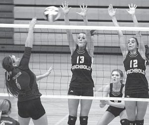 Rachel Brader (13) and Cayla Walker (12) attempt to block a Kidron spiker in the Streak Spiketacular, Saturday, Sept. 29. Archbold earned at least a share of its 22nd NWOAL title with an Oct. 4 victory at Evergreen.– photo by Mary Huber