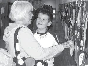 Drake Mohring, a fifth grade student at Archbold Middle School, shows off his writing project to his grandmother, Cathy Mohring, who lives between Archbold and Napoleon. The two were photographed during Grandparents Day, Friday, Oct. 5, which was also Drake's 11th birthday.– photo by David Pugh