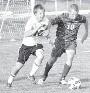 Pettisville's Caleb Yoder (10) and a Bryan Golden Bear attack the ball, Thursday, Sept. 27.– photo by Mario Gomez