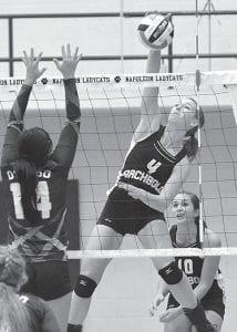 Becca Gerig (4) goes for the kill over Otsego's Lindsey Donald (14). The junior had 22 kills in Archbold's district championship victory over the Knights.– photo by Mario Gomez