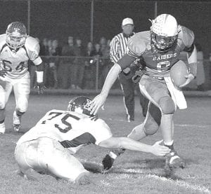 Raiders quarterback Jay Banyasz attempts to run around the outstretched arm of Archbold's Zach Zimmerman. Banyasz ran for 281 yards and passed for 177 in Columbia's 39-34 victory.– photo by Mario Gomez