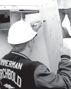 Zach Zimmerman, a member of the Archbold High School STEM (Science, Technology, Engineering, Math) Club, signs the inside of one of the covers over the wind turbine rotor hub, Friday, Nov. 2, before the first attempt to lift it into place. The cover also was signed by other STEM Club members, school officials, and school board members, among others.– courtesy photo