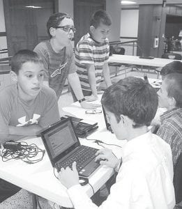 Pettisville Schools held a mock election, Thursday Nov. 1. Students from third through 12th grades chose Mitt Romney for president, 205-95. But exit polling conducted by Jason Mansfield's sixth grade class showed it wasn't a solid sweep for the Republicans. Eighth graders supported Obama 21-11. Seniors went for Romney, 12-1. In the primary grades, youngsters chose book characters Gerald and Piggy over Henry and Mudge, 86-14. Top: sixth graders Devin Beltz, Ryan Rufenacht, and John Burling, facing the camera from left, stop at the exit polls and are interviewed by Logan Rufenacht and Stetson Aeschliman. Bottom left: poll worker Justin Girdham, a fifth grader, hands out a ballot. Bottom right: Heather Sauder, a fifth grader, prepares to mark her ballot.– photos by David Pugh