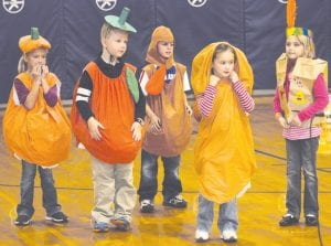 Students in the second grade classes of Kristin Shields and Lori Coressel at Archbold Elementary School entertained their grandparents at a special program featuring music, poetry, dramatic readings, and even some rap, Monday, Nov. 12. Above, from left: Carlee Meyer plays the role of the pumpkin; Cole Yunker, the apple; Krayton Kern, the turkey; and Brayton Huffman, the yam, while Rebecca Stevenson portrayed the mother in the story being told. Right: Portraying Native Americans are, from left: Corbin Stamm, Landon Stamm, Ben Dowdy, and Ethan Stuckey.– photos by David Pugh