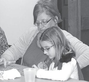 Kylee Miller, 8, Ridgeville Corners, loves to attend feather parties. Above: She and her aunt, Kim Waldvogel, Stryker, play bingo at the Archbold Fire Department Feather Party, Saturday, Nov. 17. Approximately $10,000 to $11,000 was raised. Right: Miller is excited after winning a bingo at the Ridgeville American Legion Feather Party, Friday, Nov. 16.– photos by Mary Huber