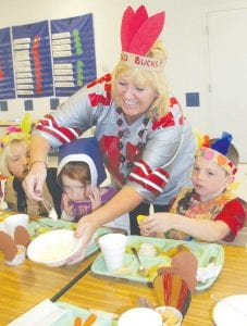 """The annual Kindergarten Feast, which teaches Archbold kindergarten students about Thanksgiving, was Friday, Nov. 16. Top: Tammy Deskins, a preschool teacher and obviously a member of the """"Buckeye"""" tribe, helps with the meal. From left are Leah Nofziger, Trisha Rupp, and Joel Mazur. Right: Tyler Perry has trouble with his costume.– photos by David Pugh"""
