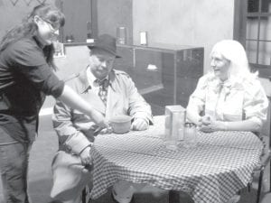 """In a scene from the Archbold Community Theatre production of """"Death by Chocolate,"""" Bobbie Sue, played by Teresa Van Sickle, left, Archbold, serves a killer Death by Chocolate to Nick Noir, a private eye played by Jeff Patterson, Archbold. Looking on is Coco Purvis, played by Susan Dominique, Archbold.– courtesy photo"""