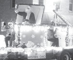 Santa and Mrs. Claus pop out of jack-in-theboxes as part a Girls Scouts of Western Ohio float in the Archbold Parade of Lights.– photo by David Pugh