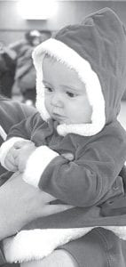 Five-month-old Hollyce Baun, Archbold, was dressed for the season. She was one of many children who visited Santa Claus after the Parade of Lights.– photo by David Pugh