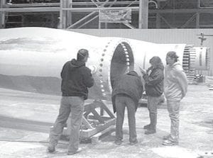 Workers from Global Blade Technology, Evansville, Ind., put the finishing touches on the last blade for the Pettisville School District wind turbine. An official from Marous Brothers, Willoughby, reported to Steve Switzer, superintendent, Monday that blades one and two were being weighed. The first coat of paint was to be applied to the third blade on Tuesday. The first two blades were to be shipped from the Indiana plant at noon today, and arrive Thursday; the third won't leave the plant until early Thursday morning. Plans call for the blades to be installed Friday.– courtesy photo