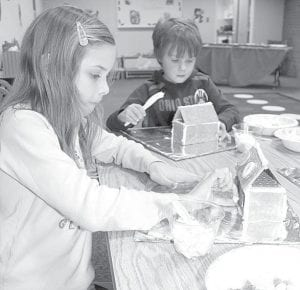 Making gingerbread houses at Christmas is a tradition at Archbold Community Library. Allison Roehrig, 8, left, and Eli Riegsecker, 6, Archbold, craft their houses out of graham crackers, using frosting for mortar and bits of candy for decoration. Several bits of mortar frosting went into little mouths.– photo by David Pugh