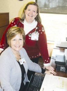 Patti Finn, standing, Fulton County Health Center new chief executive officer, with Janice Fitzenreiter, administrative assistant. While Finn has been on the job just three months, she's been an FCHC employee, in several positions, for 29 years.– photo by David Pugh