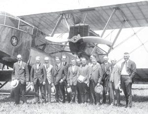 Town mayors from throughout Northwest Ohio boarded a Martin MB1 airplane to demonstrate to the public the speed and safety of air travel in the 1930s. The third person from the left is Garnet Quedo Morgan, an Archbold councilman and owner of the Red Cross Drug Store. Going aloft was a daring experience, perhaps like Neil Armstrong landing on the moon.– Antique photo from the collection of Jim Frey, great- grandson of Mr. Morgan