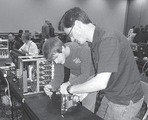 "Matt McCoy, left, helps Stephen Harnish build the computer minicluster ""LittleFe"" at SC12, an international supercomputing conference in Salt Lake City, Utah.– courtesy photo"