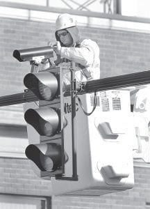 A worker from U.S. Utility, Perrysburg, installs a traffic-detecting video camera at the intersection of North Defiance and Holland streets, Friday, Jan. 4. The cameras replace old-style loop detectors.– photo by Mary Huber