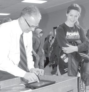 Brent Gnagey, technology director for the Archbold Area School District, sets up Jessica Lindsay's iPad tablet computer at Archbold High School, Thursday, Jan. 17. Over four days last week, Gnagey and others collected the tablets, which are provided by the school to the students, updated the software, and redistributed them. All AHS sophomores, including Lindsey, had their iPads updated on Thursday.– photo by David Pugh