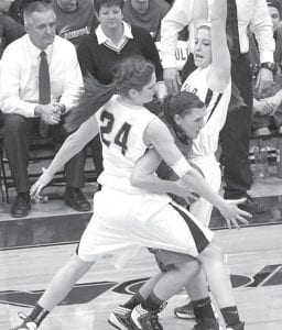 Jesse Fidler (24) and Cassidy Williams give Alyssa Reed no room to maneuver.– photo by Mary Huber