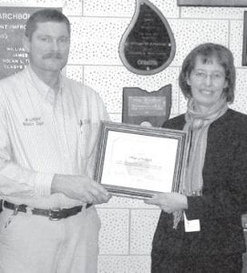Scott Schultz, left, superintendent of the Archbold water treatment plant, receives a plaque from Barb Lubberger, of the Ohio EPA, recognizing Archbold for completion of a source water protection plan. The plaque was presented Monday, Feb. 4.– courtesy photo