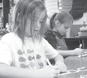 Archbold first grade students worked on projects centered around the number 100 as part of their 100-Day Celebration, Friday, Feb. 1. Top: Emma Hagerman and Hailie Hahn at work, decorating their 100-Day glasses. Right: Kadence Montalvo shows a project she made, anticipating how she thinks she will look when she is 100 years old.– courtesy photo