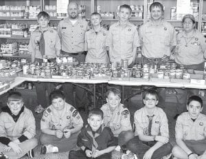 Archbold Cub Scouts Pack 263 and Boy Scouts Troop 63 donated food items to the Archbold FISH Food Pantry through their annual Scouting For Food program. This year, they collected 1,912 food items left on front porches, up about 3.4% from last year. The scouts delivered their contribution to FISH, Saturday, March 9. On hand for delivery were, front row, from left: Austin Rearick, John Ruscigno, Brennan Garrow (cub scout), Max Sauber, Brayden Hall, Zachariah Morrison. Back row: Daniel Baus; Chad Baus, scout master; Jacob Sauber; Caden Garrow; Bruce Garrow, scout leader; and Twin Ruscigno, cub master.– photo by David Pugh