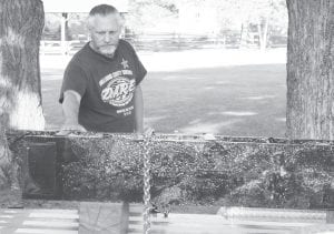 Dan Burk, West Unity, a 1976 AHS grad, lays his hand on the Fulton County 9/11 artifact in July 2011. The steel beam was part of the World Trade Center destroyed on 9-11. It will soon have a permanent home at the Fulton County Fairgrounds.