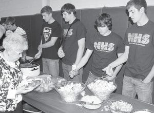 Archbold High School showed appreciation to senior citizens, Friday, April 26, with a senior citizen luncheon. Entertainment was provided by the AHS band and The Company. Top: Melba Schnitkey, Archbold, goes through the serving line, while students Devin Shannon, Tyson Dietrich, David Bontrager, and Bryce Tinsman work the event. Right: Caleb Wyse chats with Nancy Zimmerman. Aaron Rex, district superintendent, said about 130 citizens attended.– photos by David Pugh