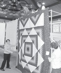 It takes several hands to prepare the annual Sauder Village Quilt Show. On ground level, from left, is Suzie Rupp, a volunteer, and Linda Stuckey, who works in the village quilt shop. On the scaffold are, from left: Lori Aeschliman and Peg Rufenacht, volunteers. The show runs through Sunday.– photo by David Pugh